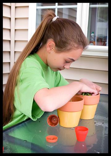 older girl re-potting plant