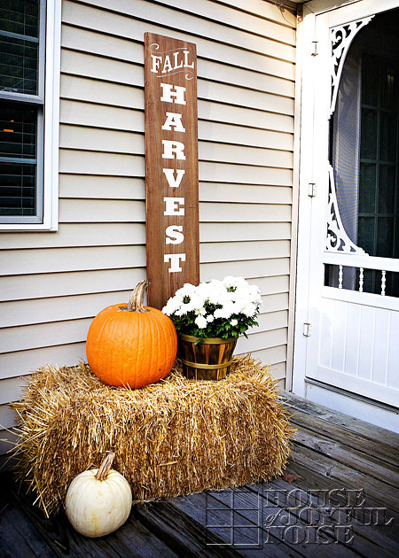 mums and pumpkin arrangement on straw bale on porch with sign